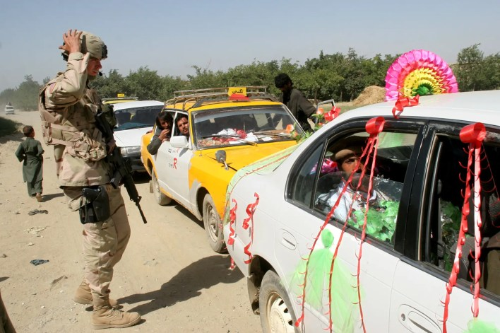 A US soldier inspects a wedding car at a checkpoint in a crossroad near Bagram air base and detention center, north of Kabul, Afghanistan, Tuesday, July 12, 2005.