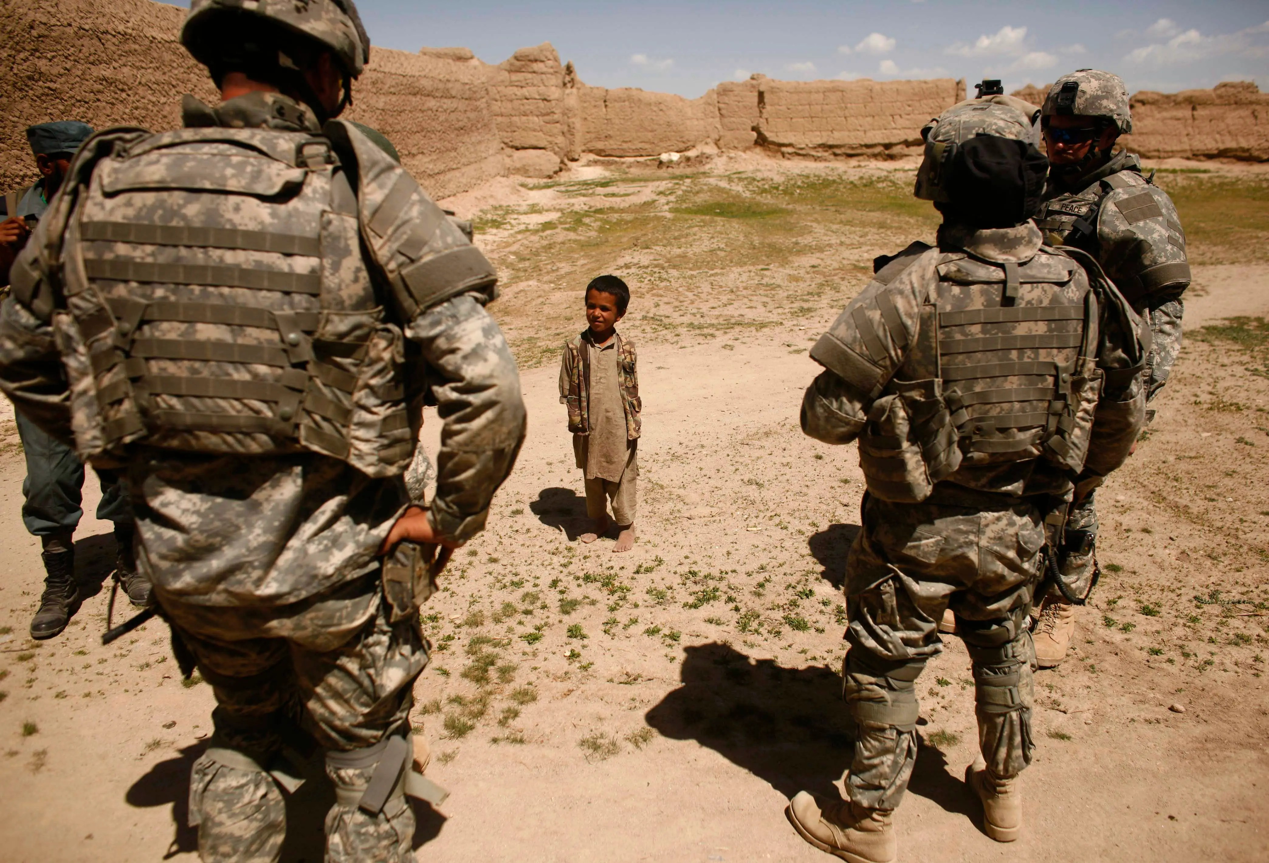 An Afghan boy looks at US soldiers as they patrol a village near the town of Makkor, southwest of Kabul, April 20, 2007.