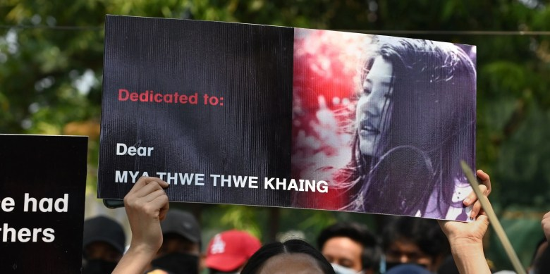 A protester holds up a poster with a portrait of Mya Thwate Thwate Khaing who died from a gunshot wound after being shot in the head last week, during a demonstration against the military coup in Yangon on February 19, 2021. (Photo by Sai Aung Main / AFP) (Photo by SAI AUNG MAIN/AFP via Getty Images)