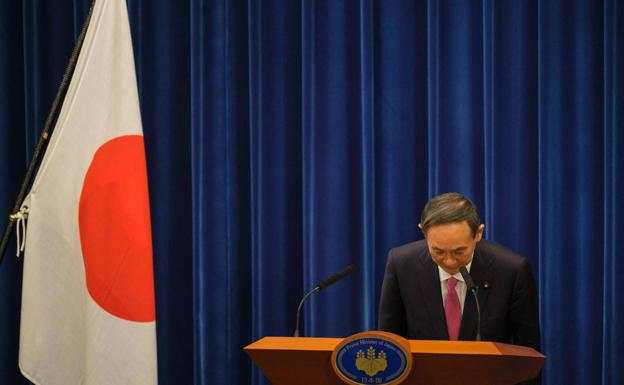 Japanese Prime Minister Yoshihide Suga greets after his appearance yesterday in Tokyo.
