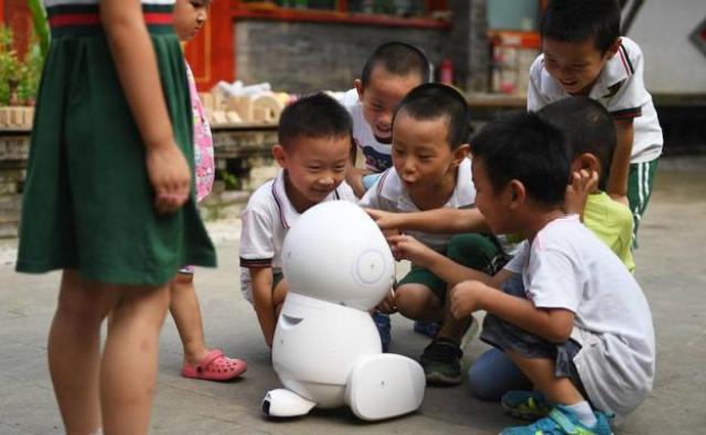 Varios niños se acercan a un robot. /GREG BAKER / AFP