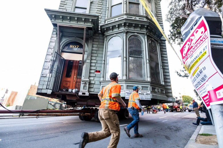 Workers pass a Victorian home as a truck pulls it through San Francisco on Sunday, Feb. 21, 2021.