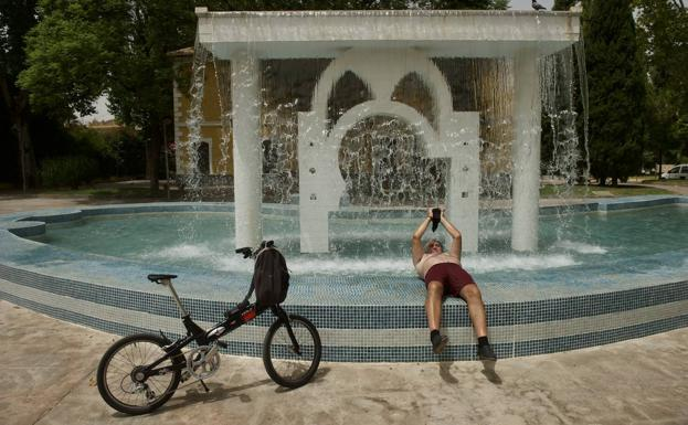 A man refreshes himself in a fountain in Murcia.