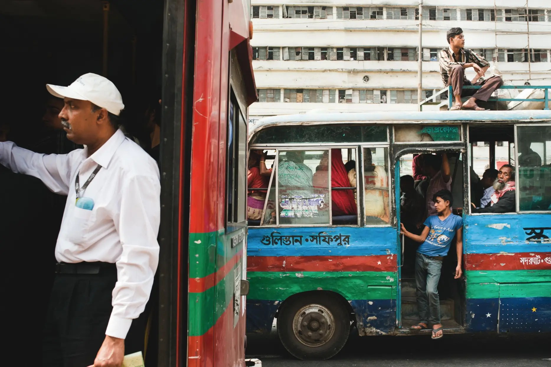 Passengers make their way through rush-hour traffic in one of Dhaka's public buses