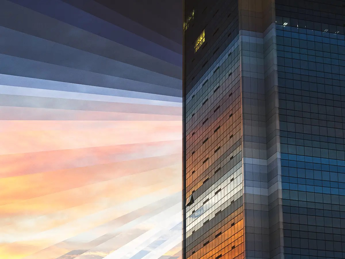 A glass building mirrors the sky in Singapore as the sun goes down over the city.