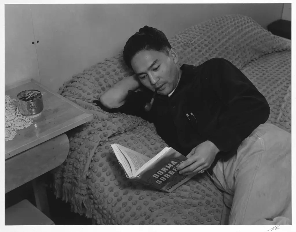 Adams also captured the recreational time at the camp, like in this image of Dennis Shimizu lying on his bed reading.
