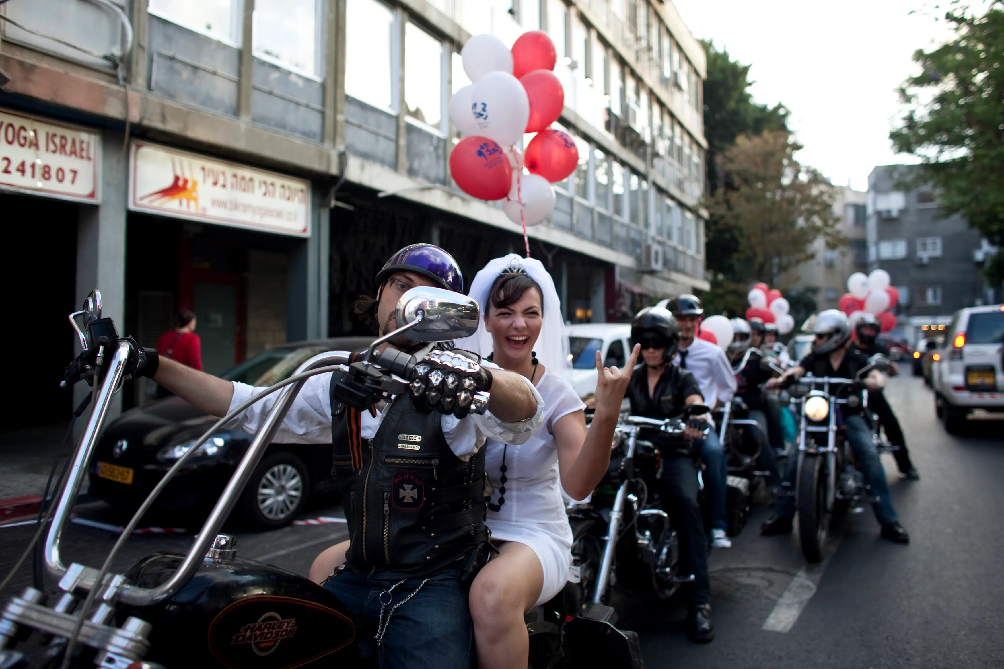 Yulia Tagil sits on the backseat of a bike as she arrives for her wedding ceremony in Tel Aviv.