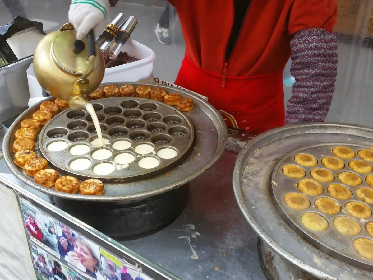 This woman poured batter from a tea kettle into a hot mold to make her tiny custard cakes.
