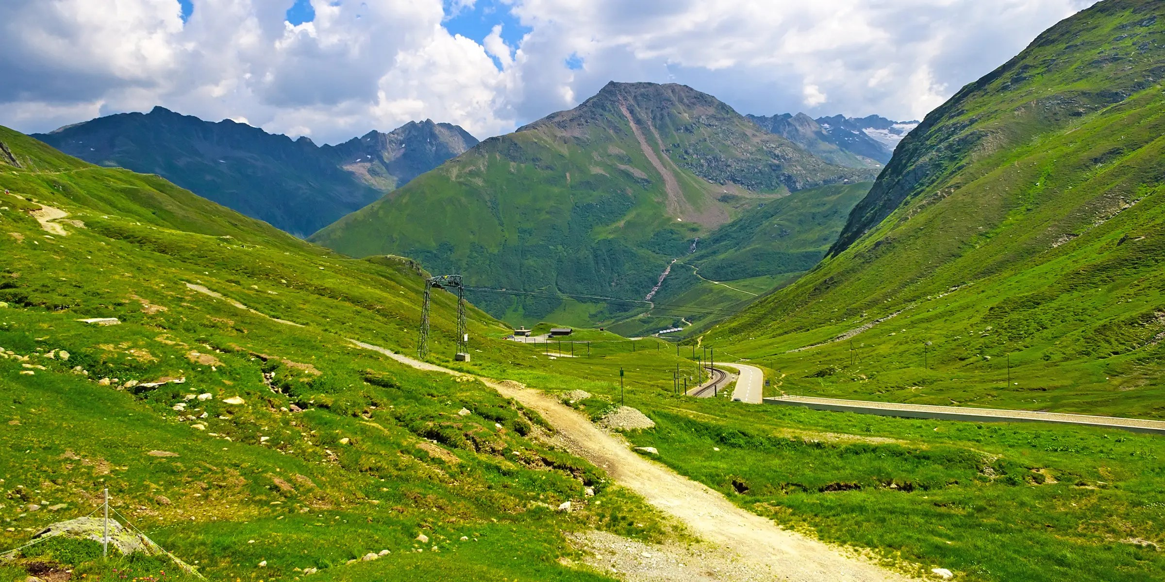The Oberalp Pass in Switzerland is a mountain road in the Swiss Alps that is 6,706 feet above sea level. The road is only open during the summer, but in the winter you can take a train ride across the pass.