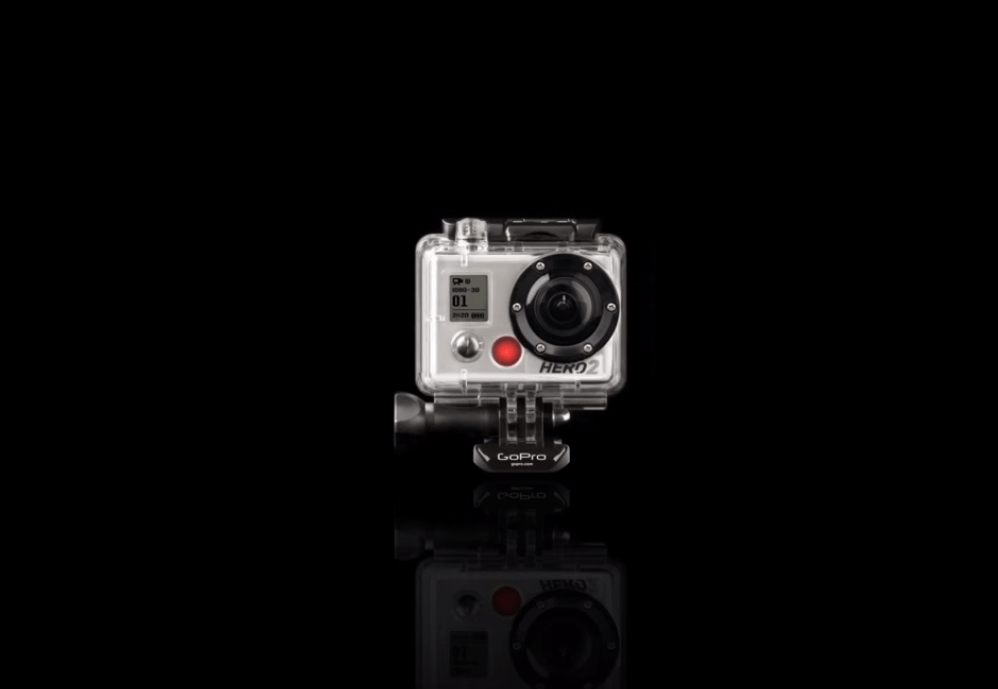 This is a GoPro. It's a camera designed for heavy-duty action, like skydiving and surfing. It goes (and survives) where other cameras can't.