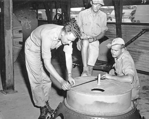 "Soldiers check the casings on the ""Fat Man"" atomic bomb. Multiple test bombs were created on Tinian Island. All were roughly identical to an operational bomb, even though they lacked the necessary equipment to detonate."