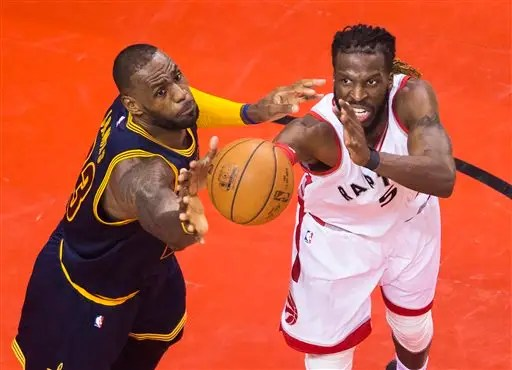 Cleveland Cavaliers forward LeBron James, left, and Toronto Raptors forward DeMarre Carroll (5) battle for the ball during the second half of Game 3 of the NBA basketball Eastern Conference finals in Toronto on Saturday, May 21, 2016. (Nathan Denette/The Canadian Press via AP) MANDATORY CREDIT