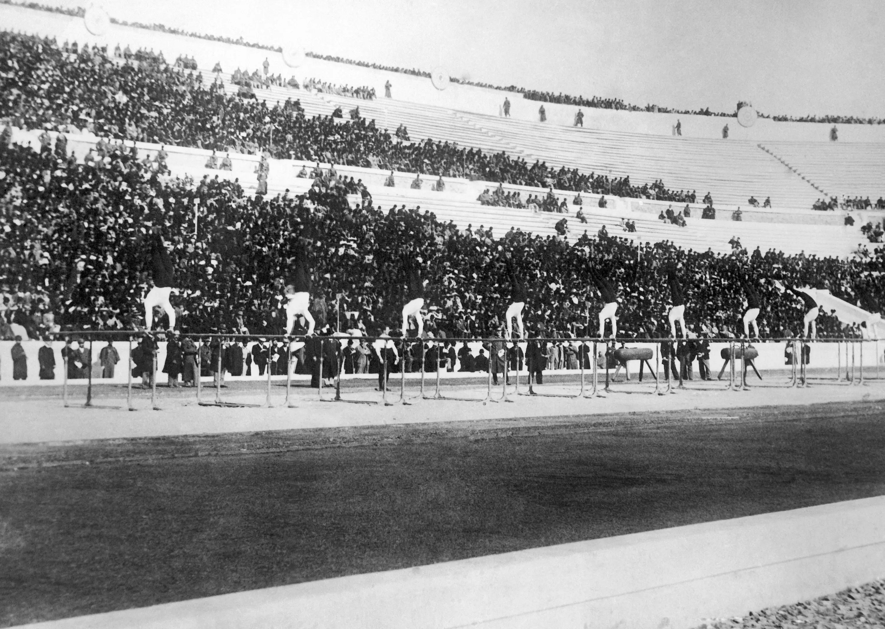 Athens, 1896: The 1896 games were the first international Olympic Games held in the modern era. They brought together the largest international participation of any event to that date, and the stadium sold out to massive crowds. In this image, members of the winning German gymnastics team show their routine on the parallel bars in front of spectators.
