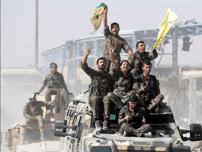 Syrian Democratic Forces (SDF) fighters ride atop of military vehicles as they celebrate victory in Raqqa, Syria, October 17, 2017. REUTERS/Erik De Castro US-backed forces clear up Raqqa after ISIS's crushing defeat US-backed forces clear up Raqqa after ISIS's crushing defeat after victory in raqqa over is kurds face tricky peace