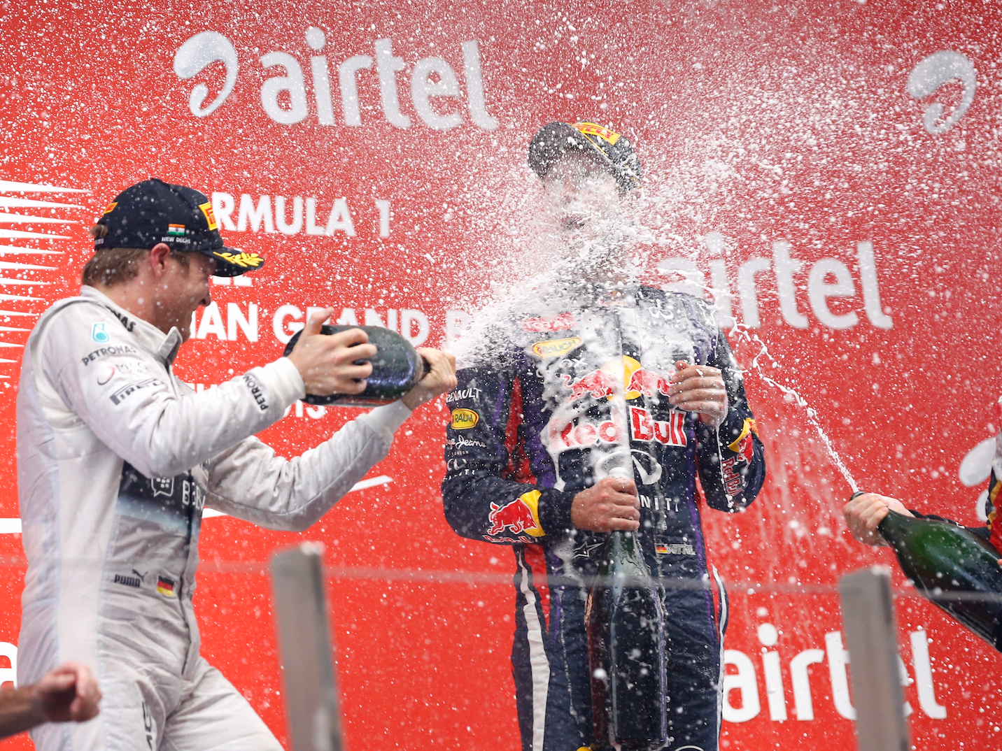 Mercedes Formula One driver Nico Rosberg of Germany (L) and Lotus F1 Formula One driver Romain Grosjean (R) of France spray champagne on the face of Red Bull Formula One driver Sebastian Vettel of Germany on the podium after the Indian F1 Grand Prix at the Buddh International Circuit in Greater Noida, on the outskirts of New Delhi, October 27, 2013.  Vettel became Formula One's youngest four-times world champion on Sunday after winning the Indian Grand Prix for Red Bull.
