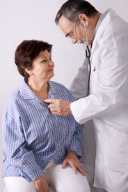 stock photo of medical doctors - elderly patient is being observed by doctor - JPG