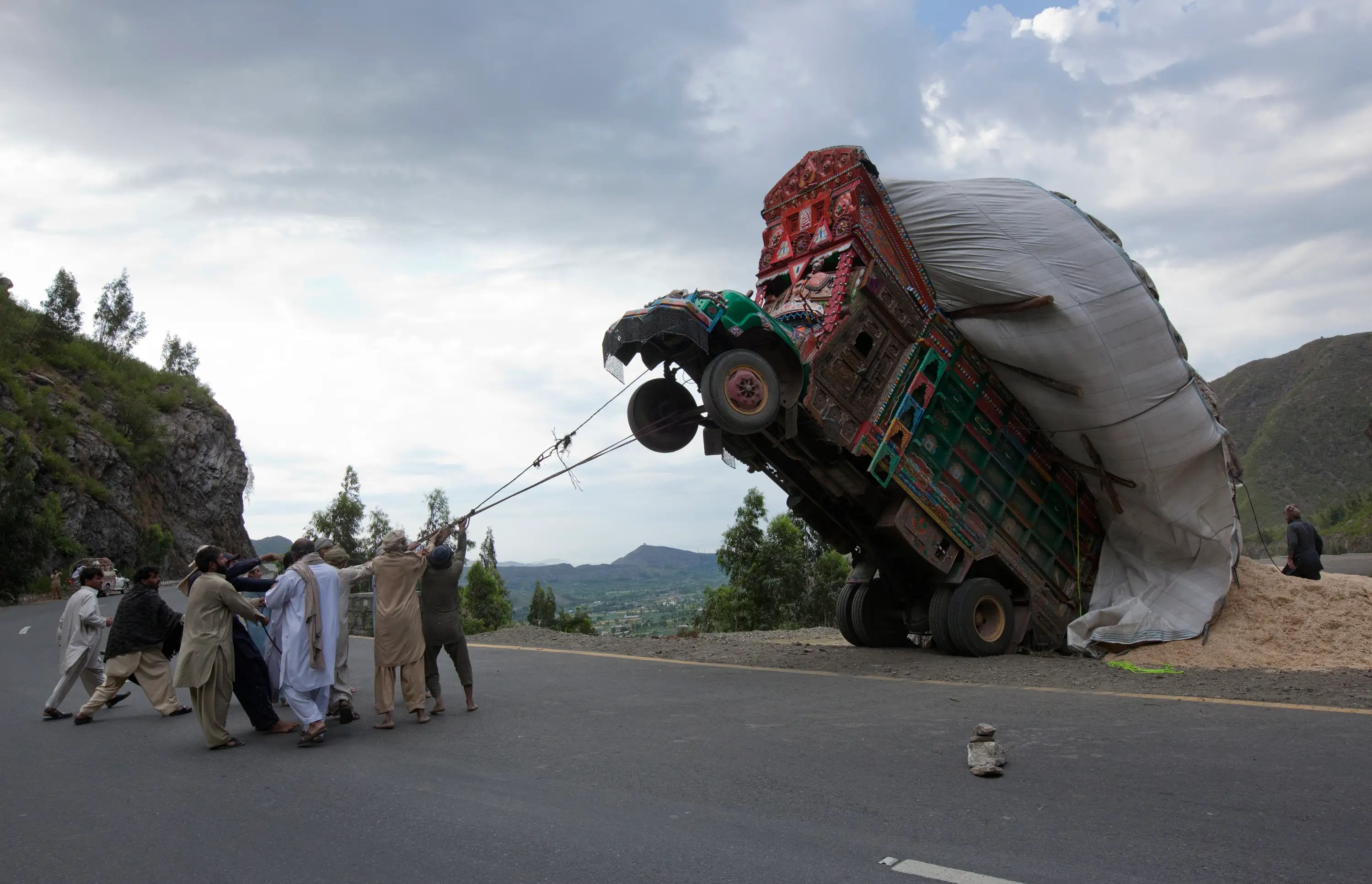 Pakistani men in Islamabad try to right a truck transporting wheat straw.