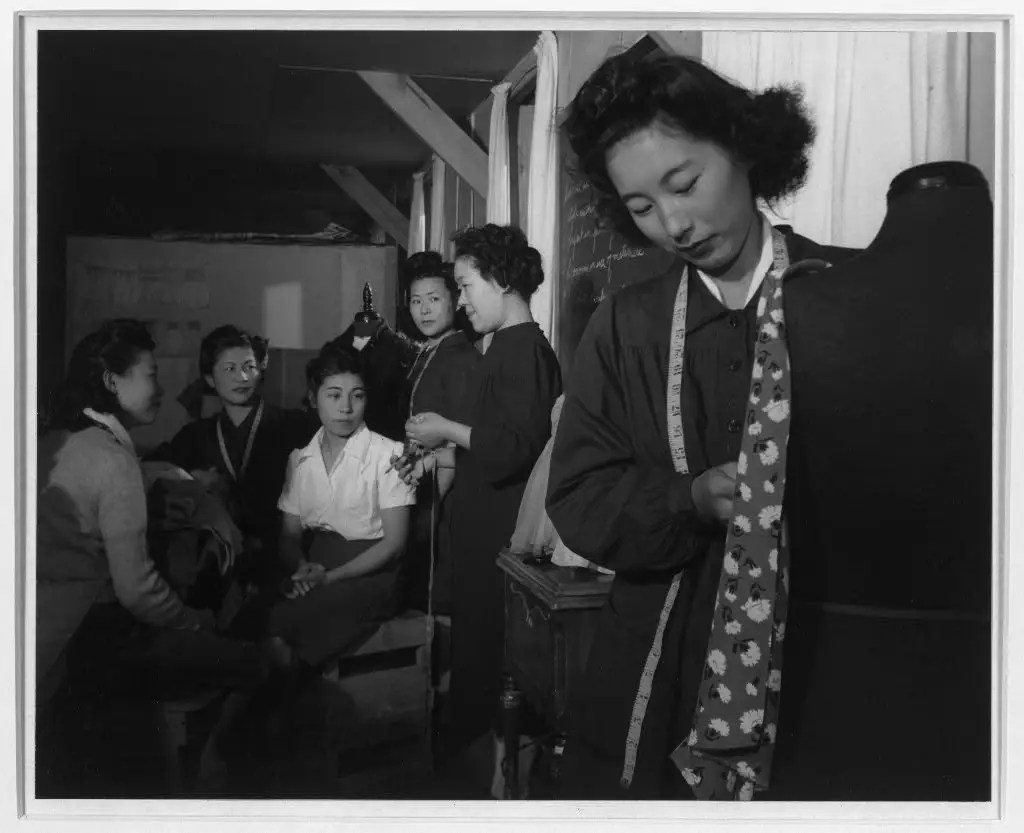 Adams' works showed the humanity of people living at the camps. Here, Ryie Yoshizawa, center, teaches a class on dressmaking.