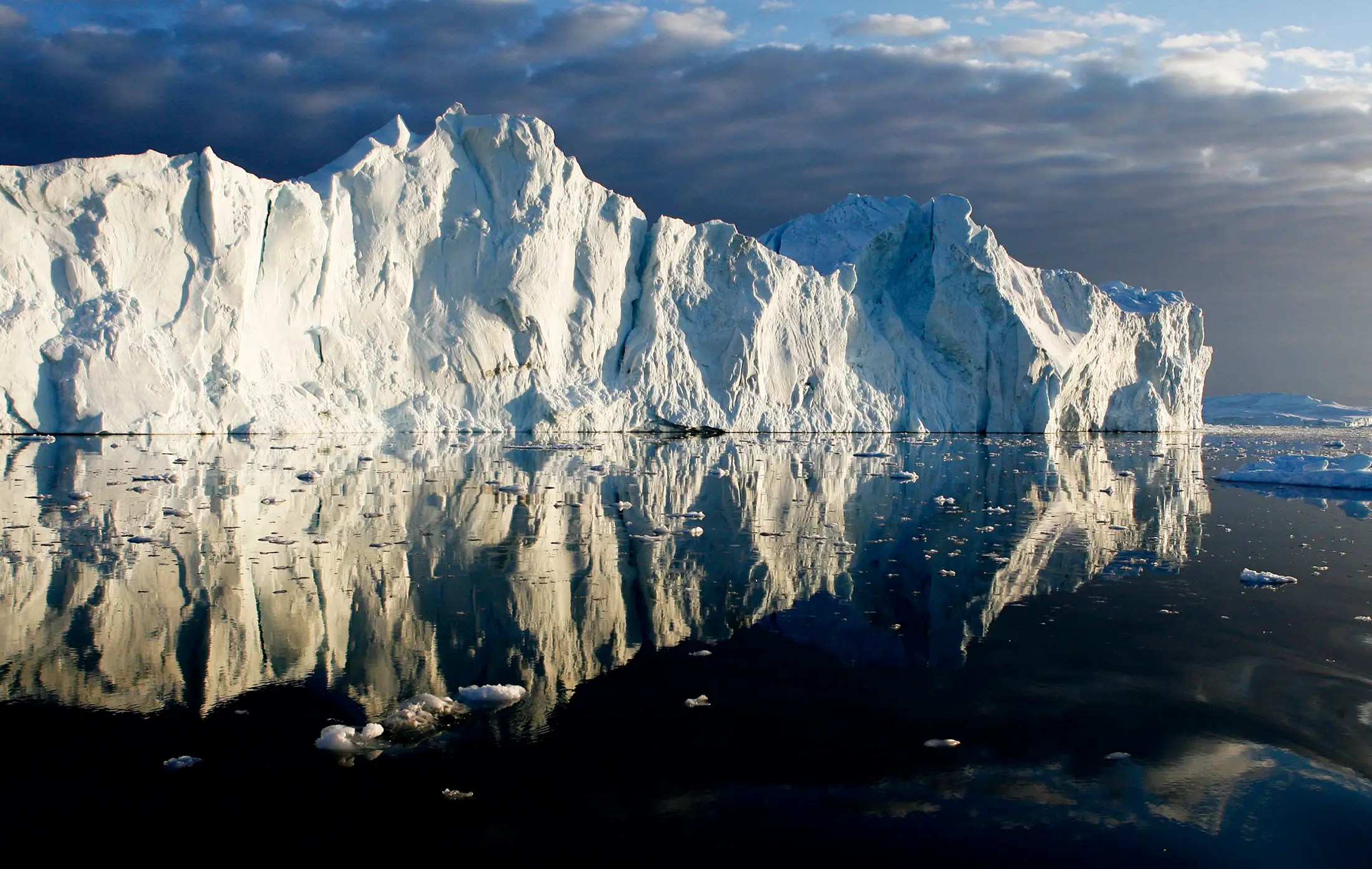 Icebergs are reflected in the calm waters at the mouth of the Jakobshavn ice fjord on the west coast of Greenland.