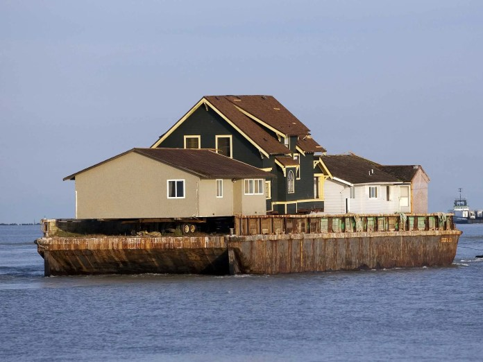 An existing home was removed by barge to make room for a separate activities building.