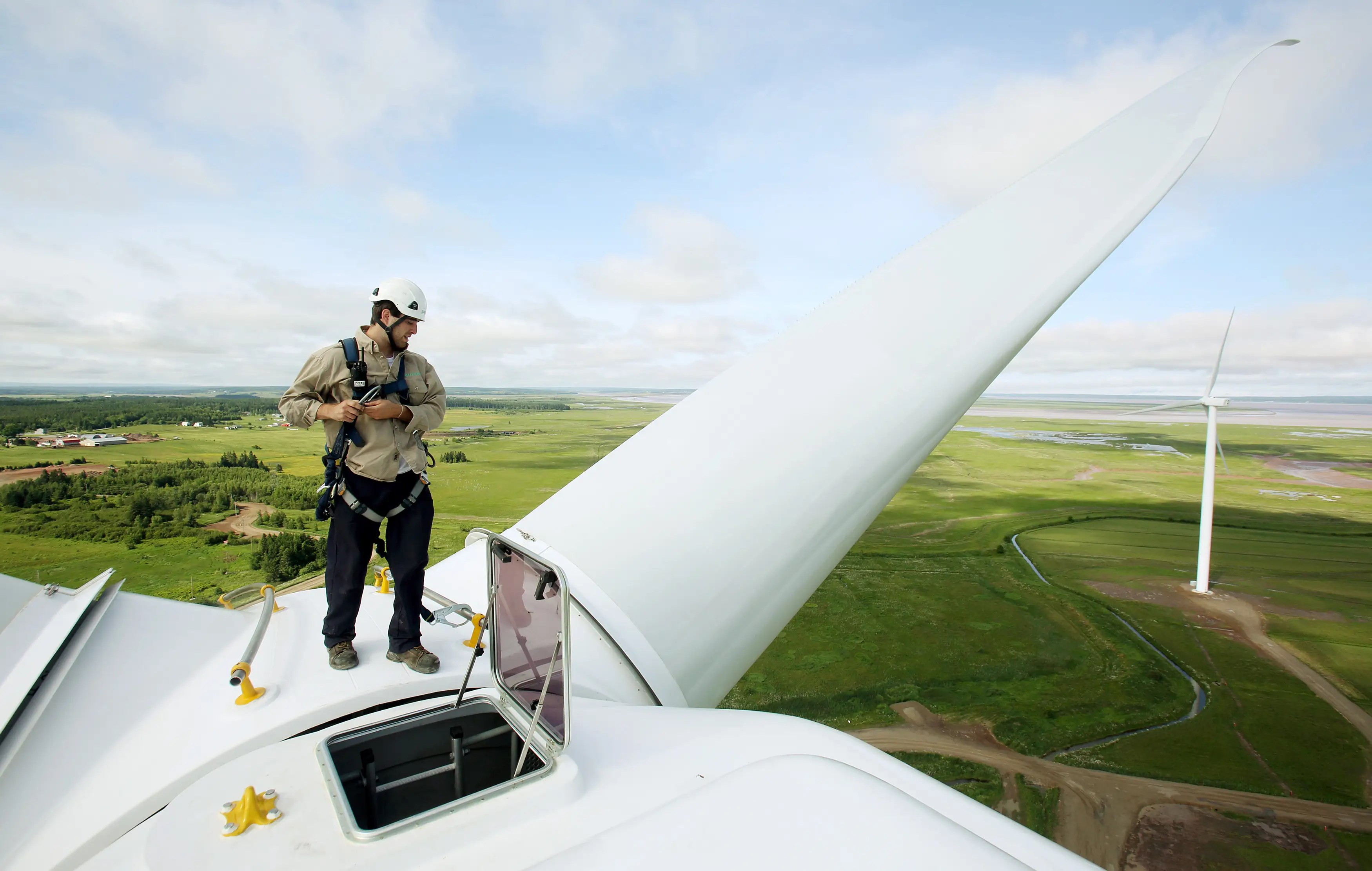Sprott Power Corporation Technician Zack Fisher stands on top one of the fifteen new wind turbines which were officially opened in Amherst, Nova Scotia.