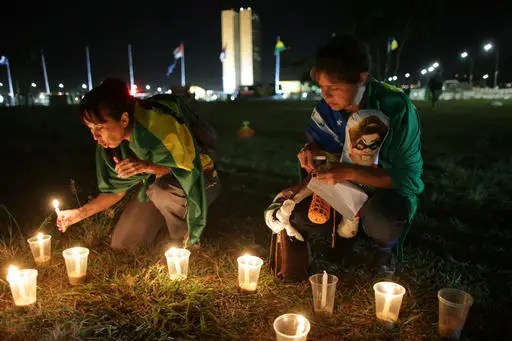 Anti-government protesters light candles outside Congress where lawmakers debate whether to oust the Brazil's President Dilma Rousseff in Brasilia, Brazil, Saturday, April 16, 2016. Sunday's vote will determine whether the impeachment proceeds to the Senate. Rousseff is accused of violating Brazil's fiscal laws to shore up public support amid a flagging economy. (AP Photo/Eraldo Peres)