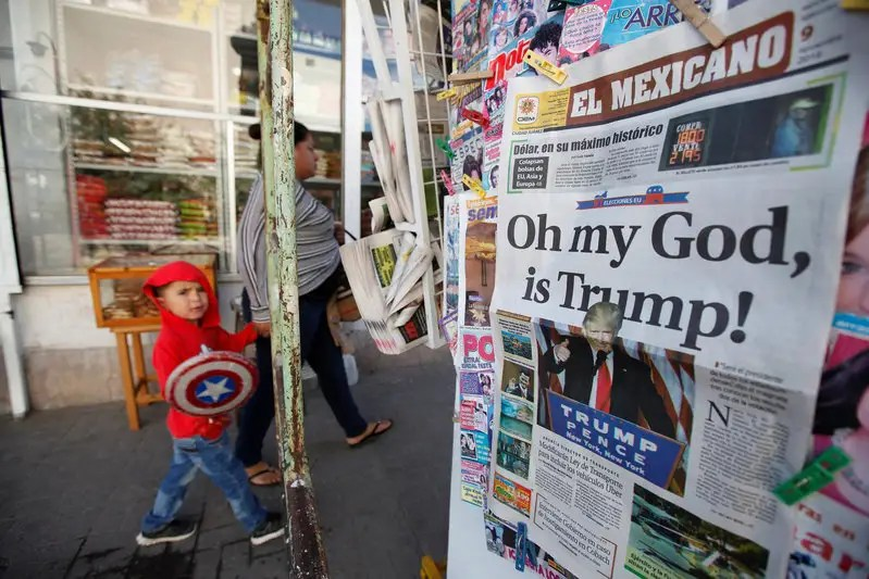 A woman and her son walk past a newspaper stand displaying a local newspaper with a headline for the victory of U.S. Republican president-elect Donald Trump, in Ciudad Juarez, Mexico, November 9, 2016. REUTERS/Jose Luis Gonzalez