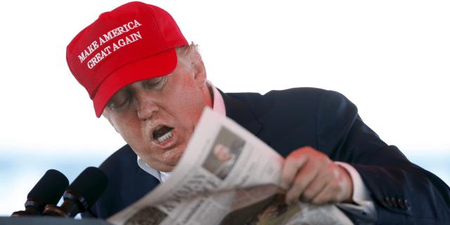 trump reading newspaper maga hat