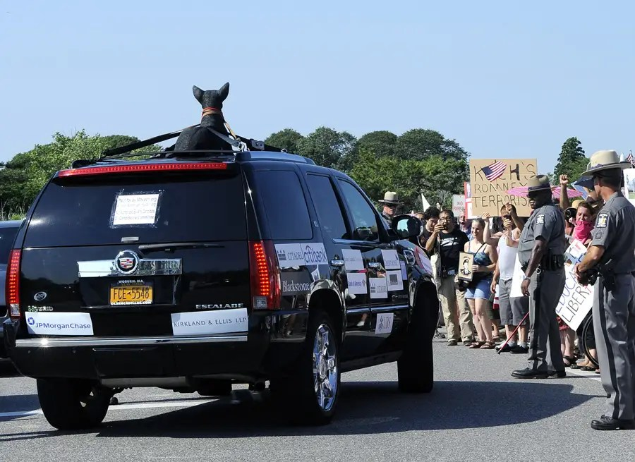 """The """"Romney Mobile"""" cruises past activists, with a fake dog tied to the roof."""