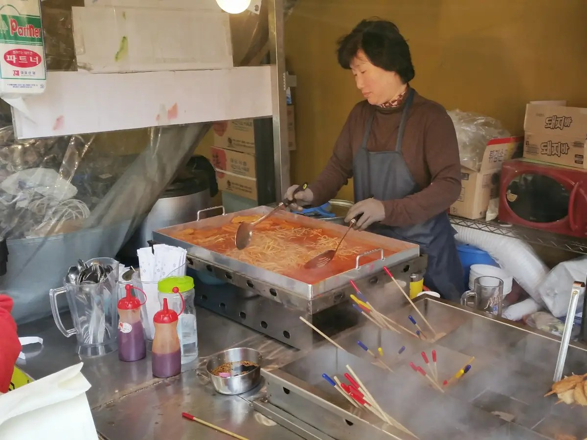 This woman was making noodles in a spicy red sauce.