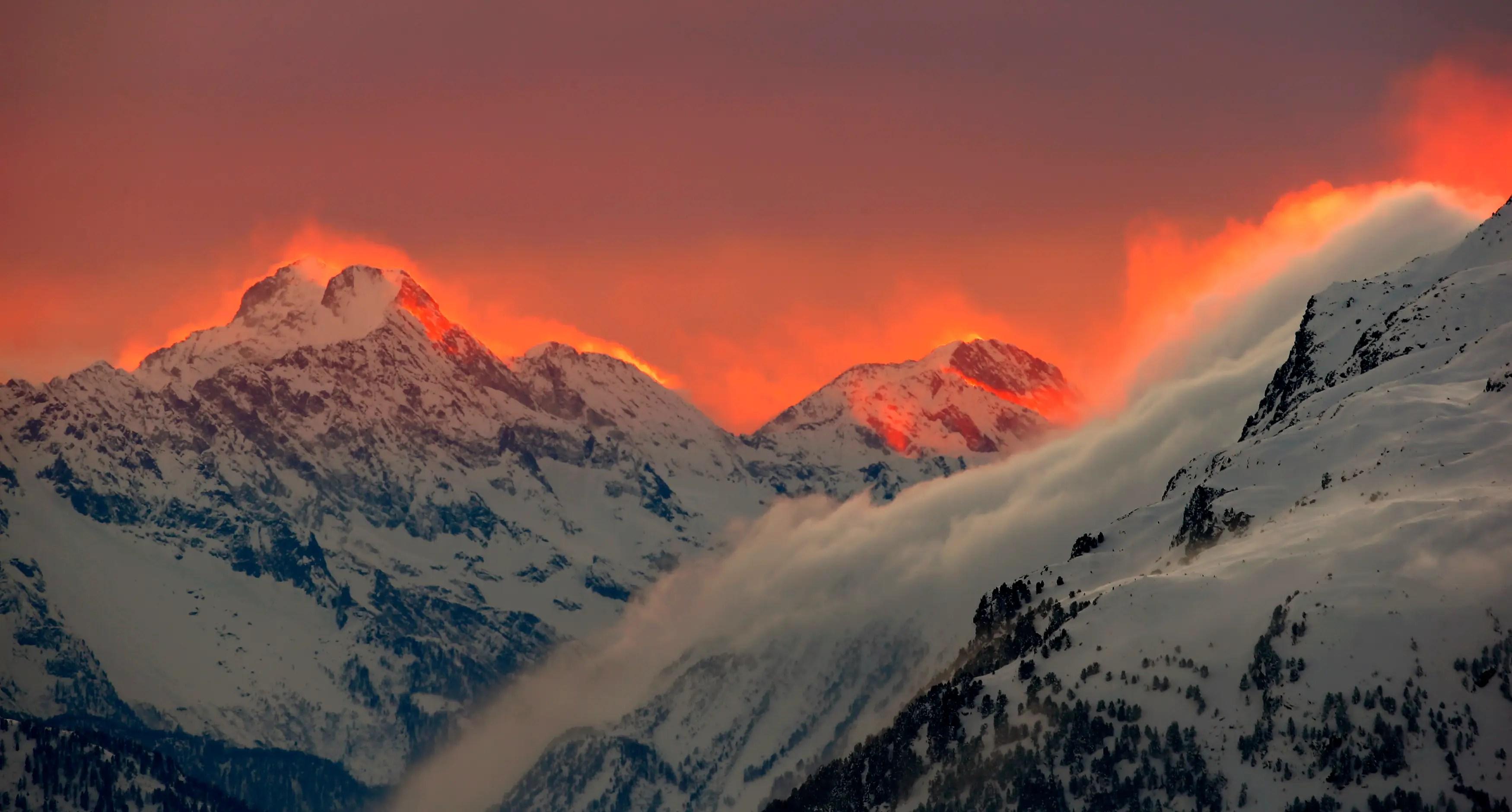The sunset lights up mountains near a Swiss resort.