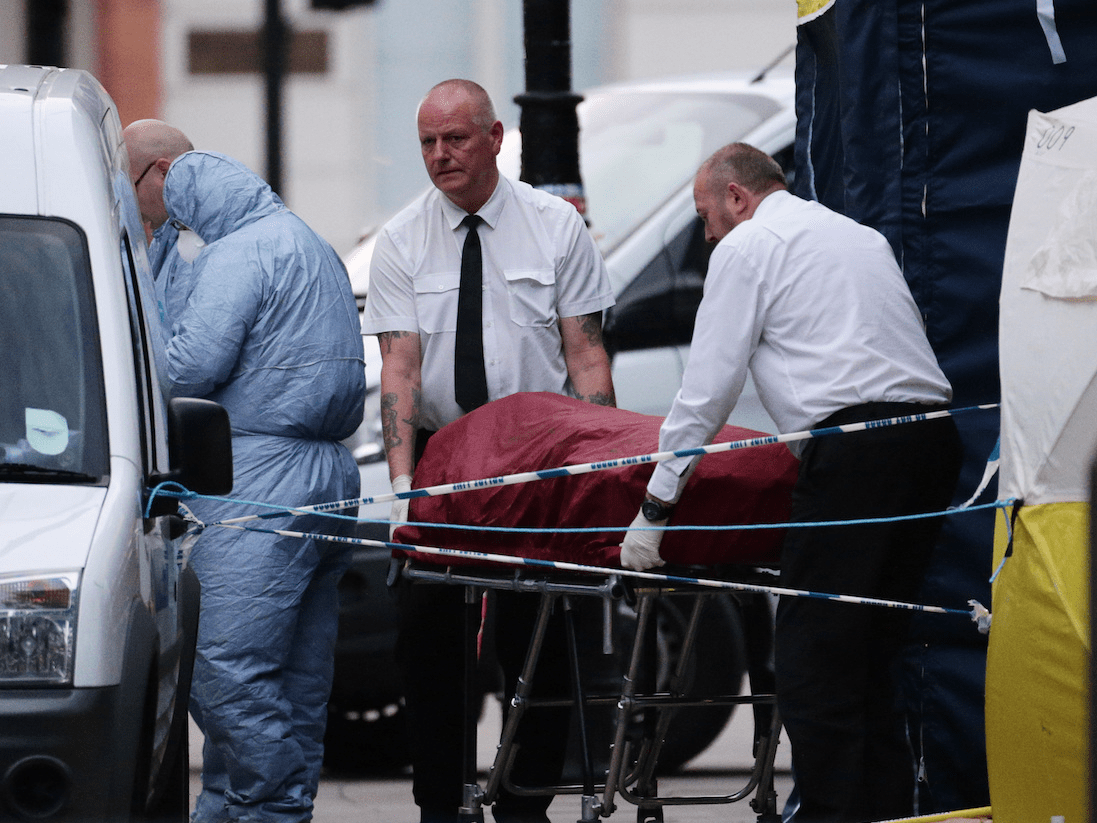 A body is removed from the scene in Russell Square, central London, after a knife attack in which a woman in her 60s was killed and five people were injured. A 19-year-old man has been arrested.