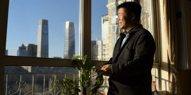 Man looks at pollution-free blue sky in Beijing from apartment