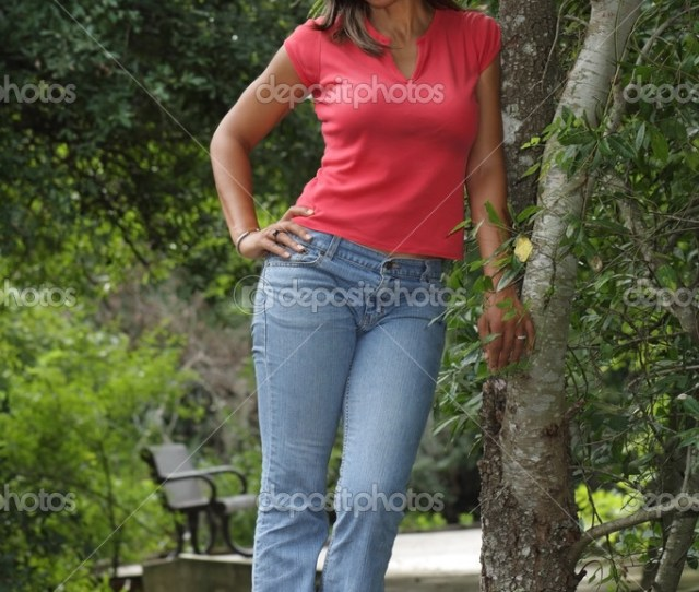 A Lovely Mature Black Woman Stands Leaning Against A Tree On A Scenic Boardwalk