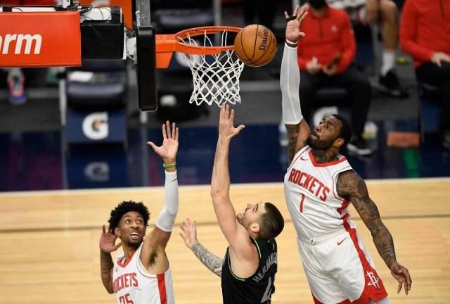 Juancho Hernangomez of the Minnesota Timberwolves shoots the ball against Christian Wood and John Wall of the Houston Rockets.