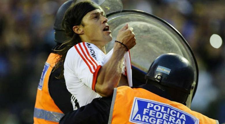 Matias Almeyda trattenuto a fatica dalla Polizia mentre fa il gesto di baciare la maglia sotto la curva dei tifosi del Boca Juniors. Foto: Archivo/Telam.