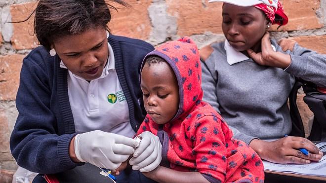 Una trabajadora de salud realiza la prueba de la malaria a un niño en Motaze, Mozambique.