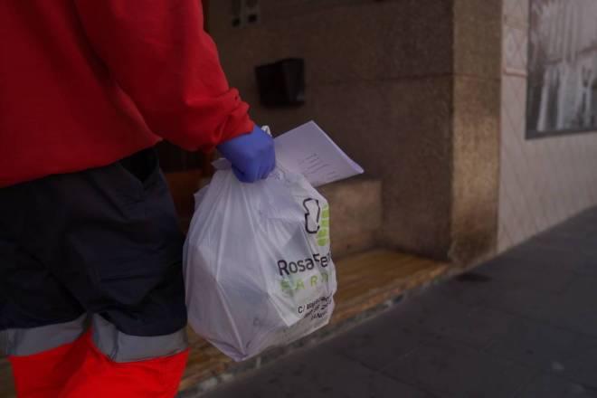 Un voluntario haciendo entrega de medicación a domicilio / Cruz Roja.