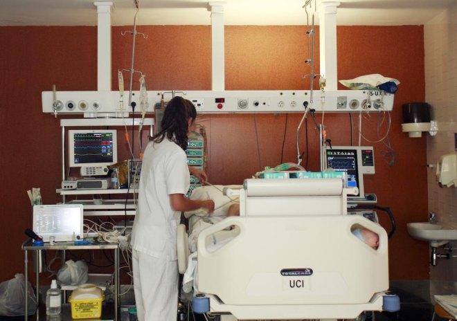 Una enfermera ante la cama de un paciente en la UCI.