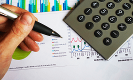 Image of a person holding a pen with a calculator and graphs.