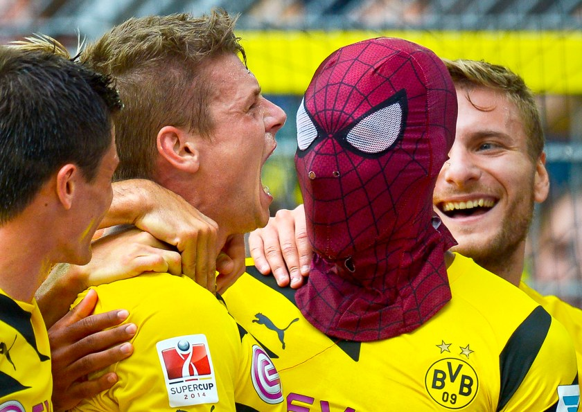 Dortmund's Pierre-Emerick Aubameyang, right, wears a Spiderman mask as he celebrates after scoring his side's second goal during the German soccer Super Cup match between Borussia Dortmund and Bayern Munich in Dortmund, Germany, Wednesday, Aug. 13, 2014. (AP Photo/Sascha Schuermann)