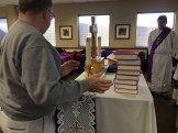 Bringing the hymnals to the altar for a blessing.