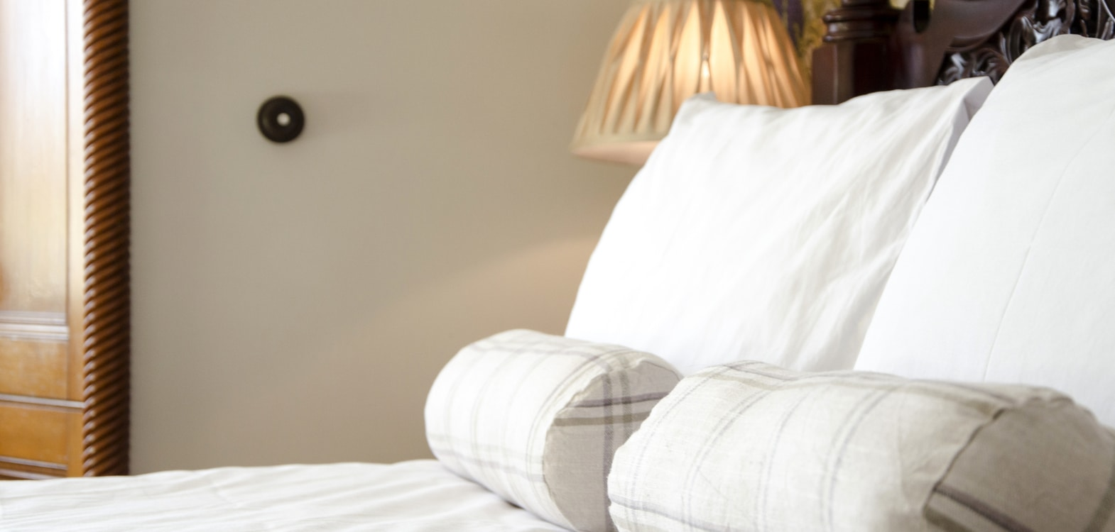 White pillows with check bolsters on a bed in the Thistle room at Strathallan Guest House