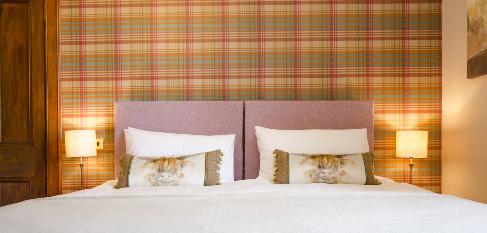 Tartan wallpaper with a zip link bed with pale pink headboards and Highland cow picture cushions at Strathallan Guest House