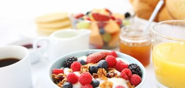 Breakfast bowl with bran flakes and mixed fresh fruit alongside a pot of jam and a glass of orange juice and cup of coffee