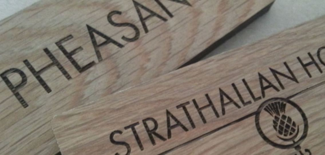 Wooden door signs with the words Pheasant and Strathallan House on them along with a thistle logo