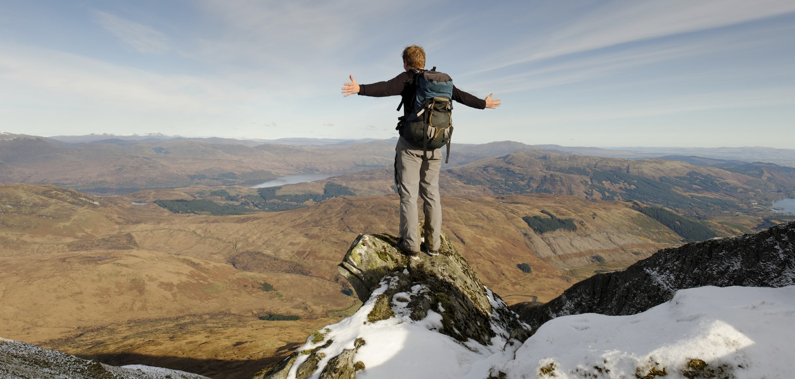A man with a rucksack with his arms open wide on top of a snow capped hill looking out across the Cairngorm mountains