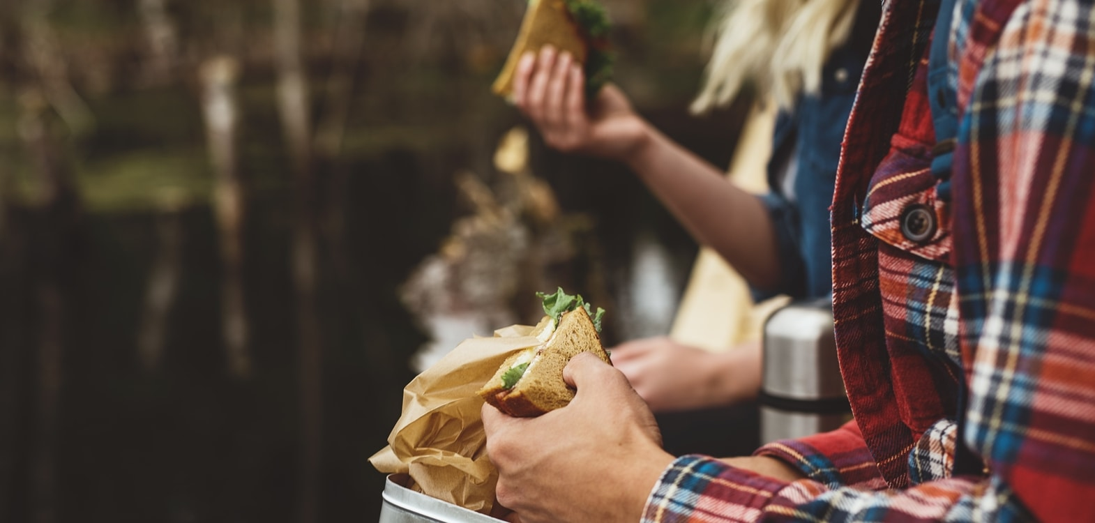 Man in a plaid shirt holding a sandwich which is part of a Strathallan packed lunch