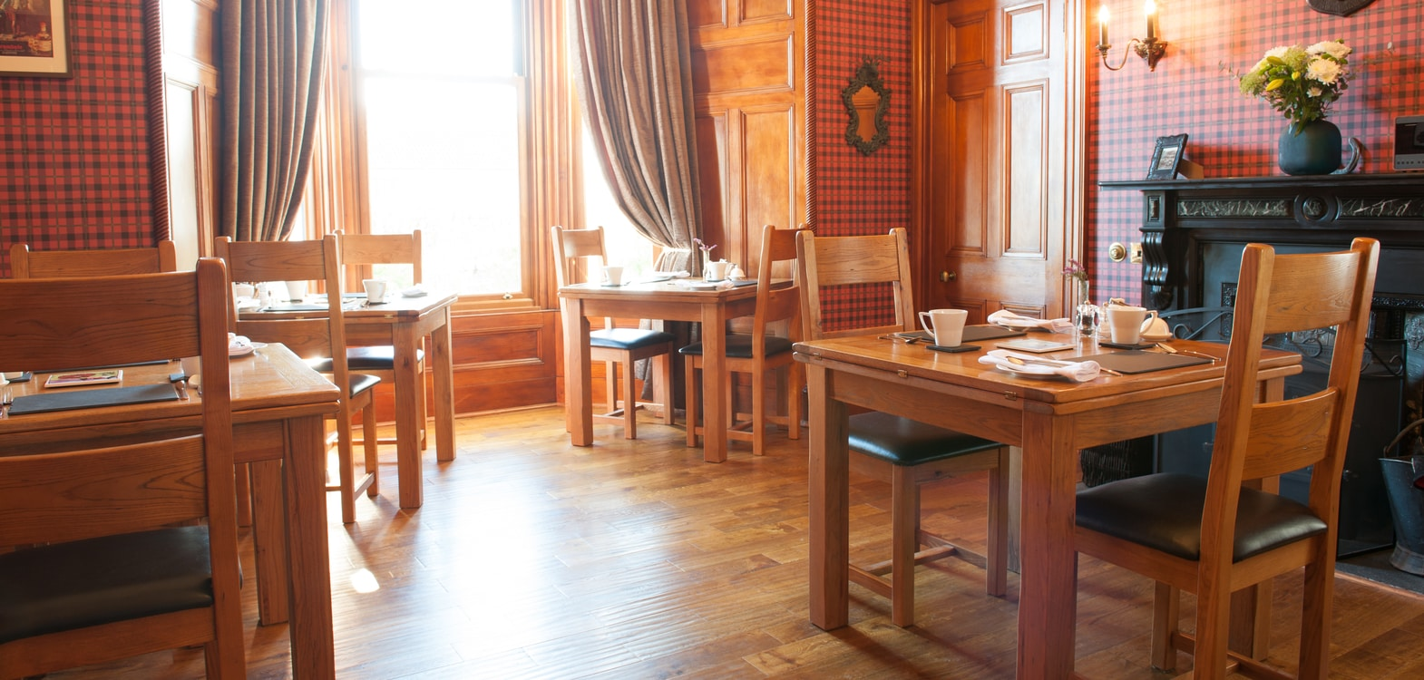 Wooden dining room tables laid up for breakfast at Strathallan Guest House in the Highlands of Scotland