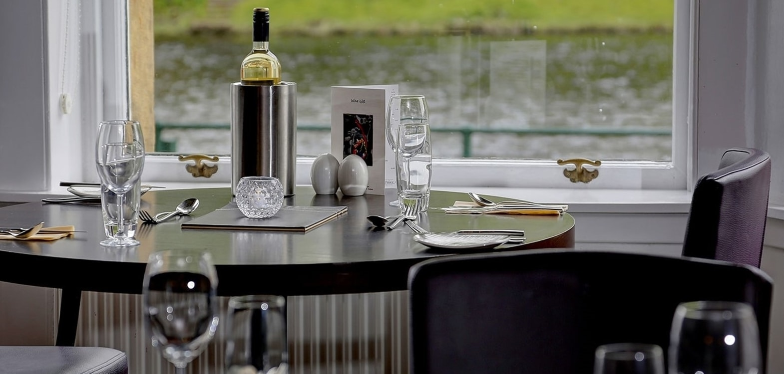 A black round dining table with a bottle of wine and glasses all set up ready for dinner guests